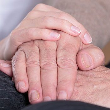 Close-up of nurse holding aged man's hands