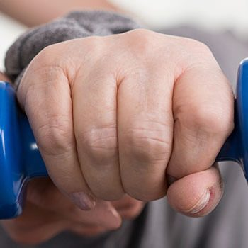 Close-up of blue dumbbell in older active woman's hand